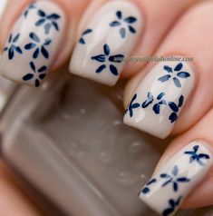 Nude nails with navy floral and crystals in middle of petals