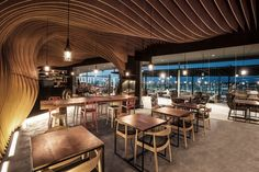 Undulating layers of timber create a cave-like interior inside this cafe in Indonesia by regional studio OOZN Style. OOZN Design installed the wavy timber Cafe Industrial, Masonite Interior Doors, Timber Slats, Interior Design Institute, Cozy Cafe, Cafe Design, Design Shop, Store Design, Architectural Digest