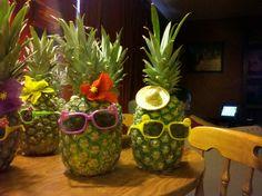 Divertidos centros de mesa para fiestas hawaianas hechos con piñas decoradas con gafas de sol y flores!