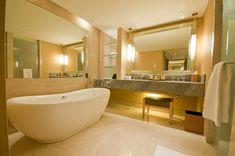 Modern bathroom with soaking tub and polished stone flooring.