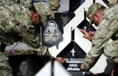 Soldiers light candles in memory of the Georgian soldiers killed during Georgia's war conflict with Russia over the breakaway region of South Ossetia in 2008, at the memorial cemetery in Tbilisi, August 8, 2014. REUTERS/David Mdzinarishvili