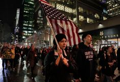 Protests after Donald Trump's victory A protester carries an upside down American flag as she walks along Sixth Avenue while demonstrating against President-elect Donald Trump, Wednesday, Nov. 9, 2016, in New York. (Photo: Julie Jacobson/AP)
