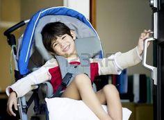 handicaps: Guapo chico de cuatro años con discapacidad en silla de ruedas abrir puerta, sonriendo con una bienvenida