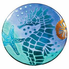 """An essential addition to your well-appointed kitchen, this lovely glass platter features a seahorse motif in blue.    Product: Serving platterConstruction Material: GlassColor: Blue and copperDimensions: 12.6"""" Diameter x 2"""" D"""