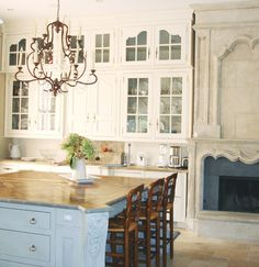 A fireplace in the kitchen...how fun. And a french limestone one, could not get better.