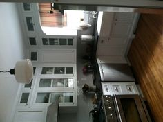 small white kitchen. Tile backsplash. Cupboards to ceiling with windows on top row