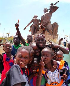A group of smiling kids in front of the African Renaissance Monument in Dakar Senegal