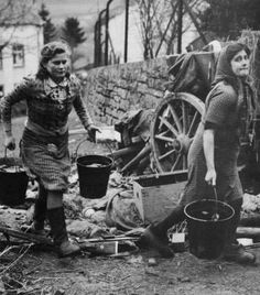 Two german 'Frauleins' (damsels) hauling water, stepping over rifles, machine guns and even the head of a Panzerfaust can be seen. Because of the absence of most men (captivity or death) much of the hard work of rebuilding Germany was their task. The characteristic term of the 'Trümmerfrauen' (debris women) found its way into common german parlance.