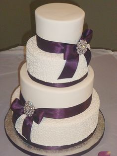 """I was really excited about doing this cake. I really wanted to do a """"bling"""" cake! I am sad that my photo wasn't a little nicer. The lighting wasn't very good and the eggplant ribbon showed up black in my photos. I messed around with some editing and improved the photo a bit. I am hoping to get into touch with the photographer for a nicer one. The bride was just a lovely person. It would be nice if everyone were so easy to work with!"""