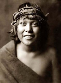Here we present a stunning image of Okuwa-Tsire, or Cloud Bird from San Ildefonso. It was taken in 1905 by Edward S. Curtis.    The image shows a Portrait of the Tewa boy, head-and-shoulders, facing front. The young boy has a happy smile on his face.