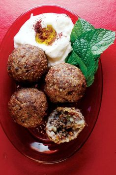 A paste of bulgur, onions, and lamb is formed into balls, then stuffed with a coarsely ground mix of spiced meat, onions, and pine nuts, and deep-fried.
