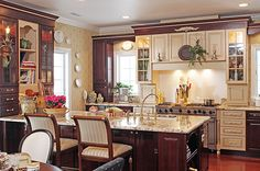 Cream cabinets make for a different take on a two-tone kitchen by Novum Custom Homes.
