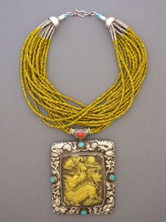An old Tibetan silver amulet with some beautiful repousee work on both the front and back of the piece, yellow bakelite, turquoise,and coral. The pendant is supported by 15 strands of small yellow and black striped glass beads from Africa, with silver heishi from Kenya and sterling silver cones and hook and eye clasp.
