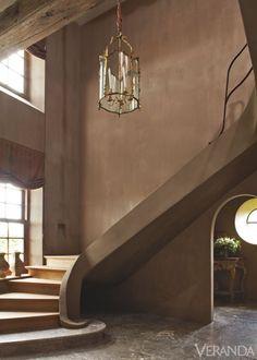 This entrance hall's sculptural cement and oak staircase, finished in gray-brown chalk plaster, curves dramatically.  Railing and oculus, Jef Van Looveren. Antique lantern. Shades in Decortex silk.  INTERIOR DESIGN BY BRIGITTE GARNIER   - Veranda.com