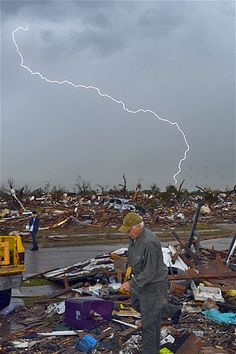 Twister's aftermath: Lightning strikes during a thunderstorm as tornado survivors search for belongings at the site of their devastated home in Moore, Okla., on May 23, 2013.