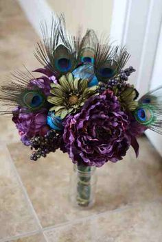 Intersperse tall feathers in floral arrangements of deep purple dahlias, red roses, and gold daisies.
