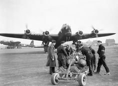 MAR 10 1942 First Lancaster bombing raid Stirling bombing up. A typical scene at Mildenhall as armourers of No 149 Squadron fit bomb carriers to a pair of while behind Stirling 'N-Nuts' runs up its engines, 10 March Air Force Aircraft, Ww2 Aircraft, Military Aircraft, Lancaster Bomber, Military Units, Ww2 Planes, West Midlands, Royal Air Force, Stirling