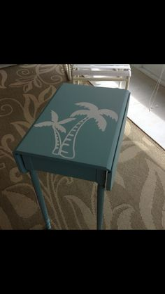 Small side table. First I painted the top white. Then I applied the Uppercase Living Palm tree and then painted it blue. I then pealed off the vinyl showing the white trees. Easy and fun. Get your vinyl from http://Linda.uppercaseliving.net