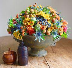Mixed arrangement of mums, dahlias, blue viburnum berries, blue thistle, poppy pods and rose hips.