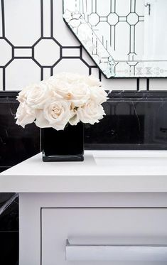 A black vase contrasted with white roses sits on a white quartz countertop accenting a white washstand positioned against black marble wainscoting.