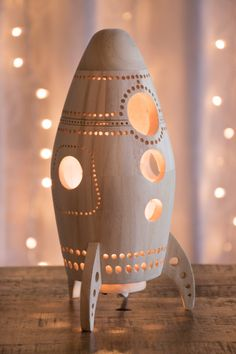 This wooden rocket ship lantern is perfect for an outer space themed nursery or childs bedroom. Its glow is bright enough to light the way in the dark, but soft enough to let your little one sleep, while casting gentle spiraling patterns on the walls and surfaces around it. --------------------  S P E C I F I C A T I O N S :  11 tall x 5 diameter 28 cm tall x 13 cm diameter  Natural bare wood finish Intended for indoor use  Light fixture: 55 (1.6 m) cord with rolling switch Clips in and is…