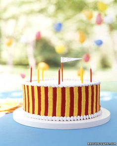 Carnival Cake  This circus-inspired two-layer cake is frosted in white, then piped in tent colors, trimmed with candy-covered chocolates, and topped with a tiny paper flag taped to a toothpick.