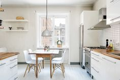 Urban condo living. The small four seater table with the hanging lamp is perfect for a small kitchen/dining space