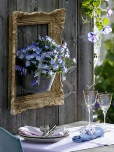 Frame your flower pots! ~ Galvanized bucket with purple flowers is hung on a wooden fence and framed with an ornate vintage picture frame to accent a small outdoor dining area