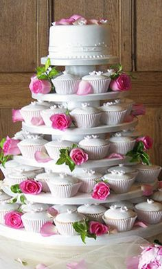 "Budget Wedding Cake Idea:  6"" fondant round top to cut, plus 36 large filled cupcakes finished in smooth flow icing w/white b/c flowers.  Have florist finish w/fresh flowers."