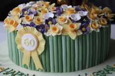 This is the 60th birthday cake I made for my friend's mum. A little horse and rider standing in a field of purple and yellow spring flowers with a few daffodills. This pic shows the detail of the 60th rosette.