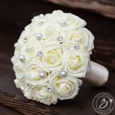 """Sparkly Gems"" medium brooch wedding bouquet with ivory roses and pearl and rhinestone gems  Traditional bouquet, classy in ivory with a spark! Our Soft Touch ivory roses are adorned with pearl and crystal buttons and pins to give this timeless piece just the right sparkle to turn heads! Bottom is lined with tulle and ivory handle. A true beauty that's simple and elegant and will work with any wedding style or color!  Listed: one bridal bouquet…"