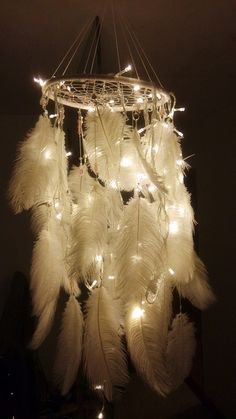 Hang beads and feathers all the way around a dream catcher, or perhaps a doily or embroidered cloth in a wooden frame. Attach a few lengths of string to the frame to hang it, and drape tiny lights through the feathers.