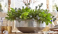 A hammered-aluminum centerpiece bowl filled with greenery provides a fresh, spring centerpiece.  - Photo: Peter Krumhardt / Design: Michelle Pulver