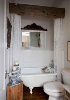 Rustic barn lumber used as a header over the shower curtain bar. Love the claw foot tub.