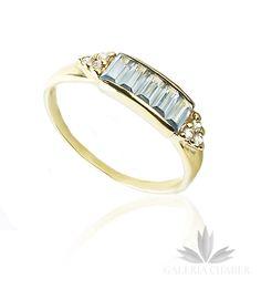 Subtelny pierścionek wykonany ze złota próby 585 z błękitnymi Cyrkoniami w kształcie prostokątów oraz drobnymi białymi Cyrkoniami po bokach. Szerokość wzoru to około 0,5 cm. Rozmiar 11. Niebieskie kamienie o prostym, aczkolwiek efektownym szlifie.