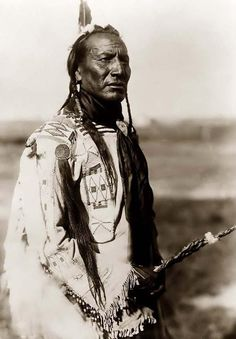 Big Mouth Spring, an Indian wearing a scalp on his jacket. It was made in 1910 by Edward S. Curtis.  The photo documents this brave in a three-quarter length portrait, standing, facing right. He has long braids with one feather in his hair. He is wearing a beaded buckskin shirt, decorated scalp lock on right shoulder. He has a black silk neckerchief.