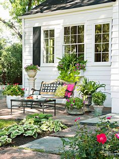 A new flagstone patio was created when the homeowners built the dining room addition. A bench, a low table, and pretty containers make the area