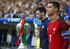 Portugal captain Cristiano Ronaldo walking past the #EURO2016 trophy.