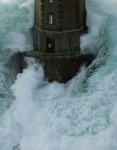 Famous photo of La Jument (France), December 1989. The lighthouse keeper, Theodore Malgorn, was taking refuge in the lantern room while waiting to be rescued from the storm.   Hearing the helicopter, Malgorn came outside thinking it was his rescuers. Just then these huge waves crashed around the lighthouse. He quickly got back inside and shut the door just in time.