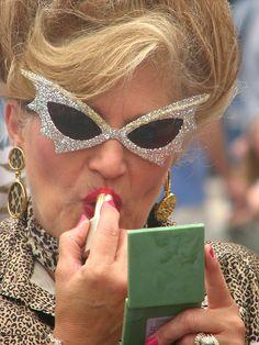 Diamond crusted cateye Hon puts on lipstick during the Baltimore hampden honfest    Make up break