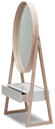 The Iona Cheval mirror is a full-length elliptical mirror framed in solid oak with a shaker-style joint and brass rivet detail at one side. The solid oak A-frame is finished in a matt white oil, allows the mirror to pivot, and supports an off-white lacquered drawer section, whose top doubles as a compact low dressing table.