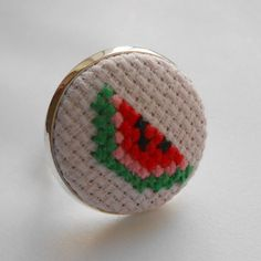 Hand sewn cross stitch ring featuring a little slice of fresh watermelon on a very pale pastel pink canvas!    Set into a silver-tone adjustable ring. Measurements approx. 22mm across.    Packaged in a simple kraft gift box.    This item will be sent standard first class post.