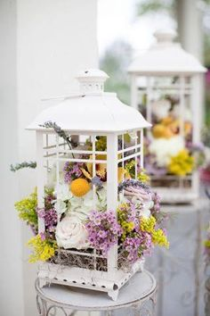 lanterns filled with flowers- we could do this in a metal lantern with neutral colored flowers inside