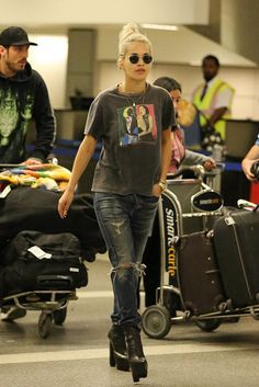 Ora makes a case for a casual-cool airport look with a charcoal graphic T-shirt, ripped denim, and sky-high platform boots.