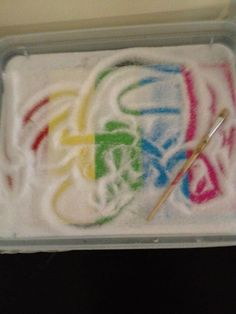 salt tray sensory play - I like the colors underneath and the paint brush