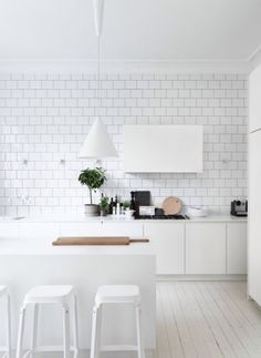 all white kitchen with subway tile, pendant light, and bar stools