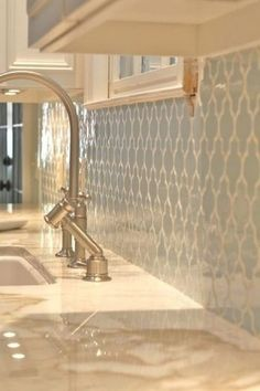 Pale Blue Tile Backsplash with White Grout against White Cabinets and Cream Countertops