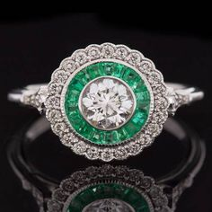 Featured here is a gorgeous diamond and emerald halo engagement ring with stunning details! This unique ring was inspired by the early 1900s and it is full of wonderful vintage charm. The center stone is a high quality G-H, VS1 round brilliant cut with alluring sparkle and life! The diamond is bright white, showing no color, and it is even better than eye clean as inclusions are very difficult to find even under 10x magnification! This ring is an incredible piece of craftsmanship because…