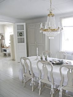 grey and white dining room. painted chairs, chandelier