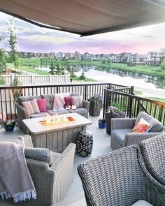 This patio with comfortable gray patio furniture and a fire table overlooking the lake is the perfect spot to enjoy a Grapefruit Rosé Sangria Outdoor Dining, Outdoor Spaces, Outdoor Decor, Rose Sangria, Fire Table, Outdoor Furniture Sets, Backyard, Chandeliers, Grapefruit Vodka